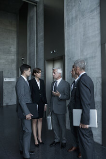 Group of businesspeople discussing at elevator - CHAF000092