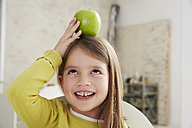 Germany, Munich, Girl sitting at table with green apple - FSF000181