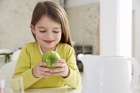 Germany, Munich, Girl sitting at table with green apple - FSF000178