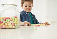 Germany, Munich, Boy with candy jar, counting candies - FSF000154