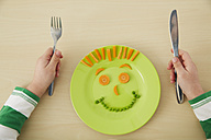 Germany, Munich , Boy eating peas and carrots showing anthropomorphic face - FSF000188