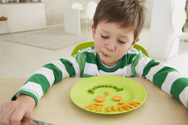 Germany, Munich , Boy eating peas and carrots showing anthropomorphic face - FSF000186