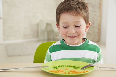 Germany, Munich , Boy eating peas and carrots showing anthropomorphic face - FSF000152