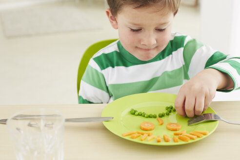 Germany, Munich , Boy eating peas and carrots showing anthropomorphic face - FSF000148