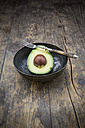 Bowl with half of avocado (Persea Americana) on wooden table - LVF000591