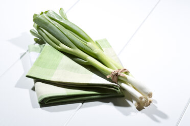 Bench of spring onions on folded tablecloth and white wooden table - MAEF007733