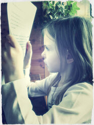 Girl reading of sheets from, Bavaria, Germany - SARF000230