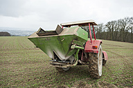 Germany, Rhineland-Palatinate, Neuwied, farmer sowing artificial fertilizer with tractor - PA000372