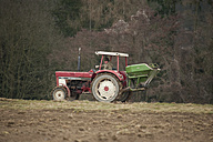 Germany, Rhineland-Palatinate, Neuwied, farmer sowing artificial fertilizer with tractor - PA000367