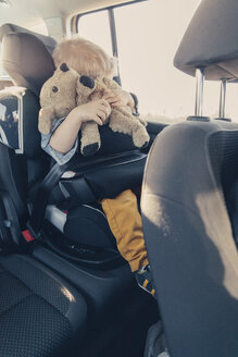 Germany, Little boy sitting in back-seat car seat, holding his stuffed animal - MFF000886