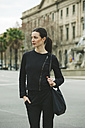 Spain, Catalunya, Barcelona, young black dressed businesswoman in front of a street - EBSF000001