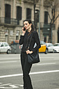 Spain, Catalunya, Barcelona, young black dressed businesswoman telephoning in front of a street - EBSF000007
