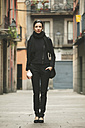Spain, Catalunya, Barcelona, young black dressed businesswoman with coffee to go in front of a street - EBSF000014