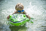Young boy swimming with swim toy - PAF000394