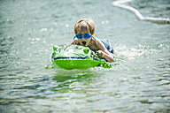 Young boy with swimmming goggles and swim toy - PAF000393