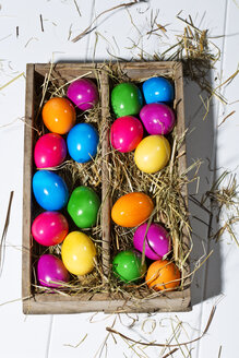 Wooden box of shiny coloured Easter eggs on white ground - MAEF007774