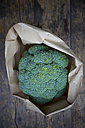 Paper bag with broccoli (Brassica oleracea var. italica) on wooden table - LVF000604