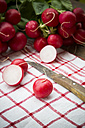 Sliced and whole red radishes and knife on kitchen towel, close-up - LVF000599