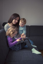 Young mother sitting with her little daughter and little son on a couch - MW000003