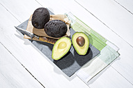 Sliced and whole avocados (Persea americana), baking paper, knife and slate on napkin and white wooden table - MAEF007820