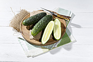 Sliced and whole cucumbers (Cucumis sativus) with knife on chopping board - MAEF007826