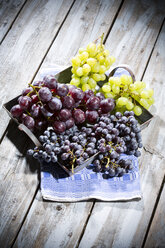 Metal tray of different green and blue grapes on kitchen towel and wooden table - MAEF007853