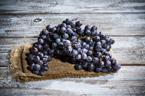 Seedless blue grapes on jute and wooden table - MAEF007855
