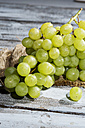 Seedless white grapes on jute and wooden table - MAEF007857