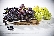 Bowl of different seedless white and blue grapes on jute and wooden table - MAEF007863