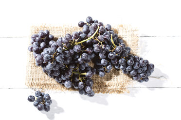 Seedless blue grapes on jute and white wooden table - MAEF007867