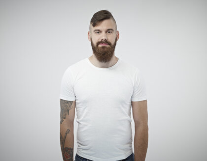 Portrait of smiling young man with shaved head, full beard and tattoo - RH000281