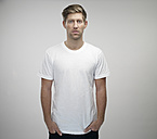 Portrait of young man with hands in his pockets wearing white t-shirt - RH000303