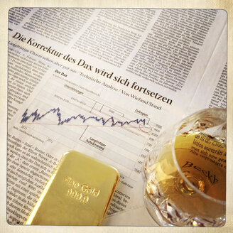 1 Kg gold bar on newspaper and glass of cognac - DR000506