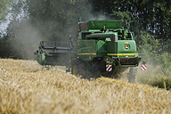 Germany, Rhineland-Palatinate, Rhineland-Palatinate, Combine harvester on barley field - PA000410