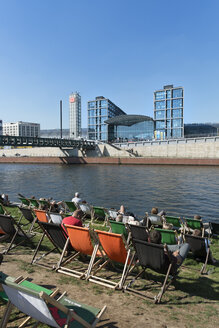 Germany, Berlin, people relaxing at riverside, central station in the background - LA000559