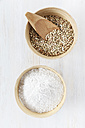 Bowl of buckwheat grains with wooden shovel and bowl of buckwheat flour on white wooden table - EVGF000431