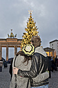 Germany, Berlin, young couple watching Brandenburg Gate and lighted Christmas tree arm in arm - CLPF000069