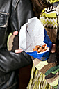 Germany, Berlin, young couple with paperbag of sugar roasted almonds, detail - CLPF000061