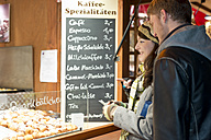 Germany, Berlin, young couple buying deep-fried pastries at Christmas market - CLPF000057