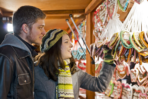 Germany, Berlin, young couple watching offerings at Christmas market - CLPF000055
