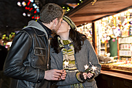Germany, Berlin, happy young couple kissing at Christmas market - CLPF000051