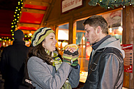 Germany, Berlin, young couple with grill sausage at Christmas market - CLPF000049