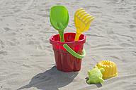 Colourful sandbox toys on sandy beach - CRF002571