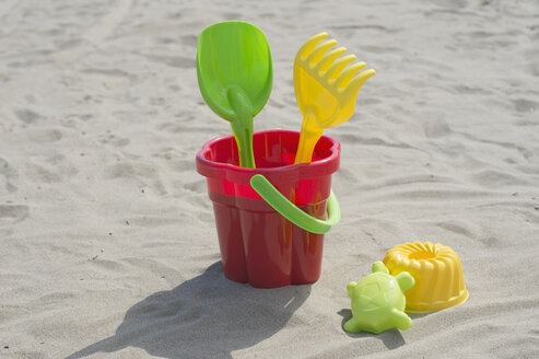 Colourful sandbox toys on sandy beach - CRF002571