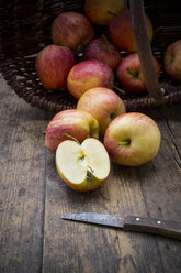 Sliced and whole red apples, basket and kitchen knife on wooden table - LVF000685