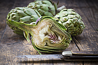 Sliced and whole organic artichokes and kitchen knife on wooden table - LVF000675