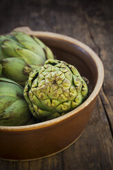 Bowl of organic artichokes on wooden table - LVF000673