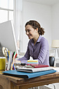 Woman at home sitting at desk with computer - RBYF000334