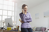 Woman leaning at desk on the phone - RBYF000344