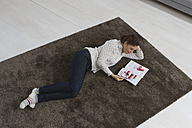 Woman lying on carpet reading magazine - RBYF000348